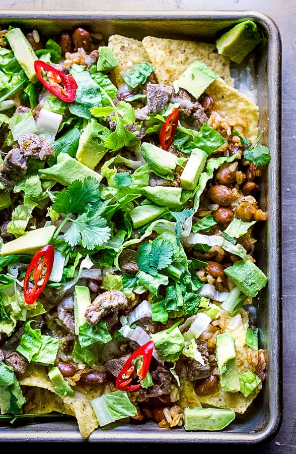 tortilla chips piled up with steak, beans, cheese, lettuce, cilantro, avocado, and peppers on sheet pan