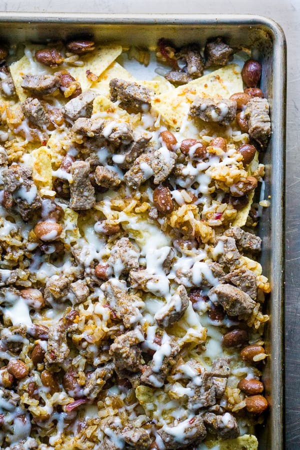 tortilla chips, steak, beans, and cheese on sheet pan