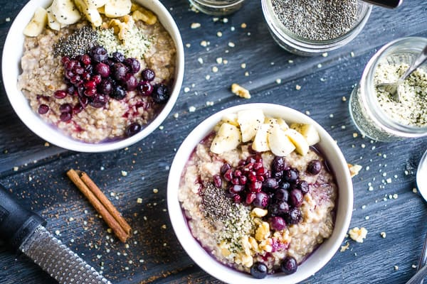 steel cut oats in white bowls with fresh fruit piled on top next to jars of hemp seed and chia seed on dark gray wood table