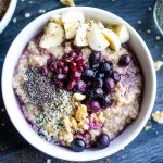 steel cut oats in white bowls with fresh fruit piled on top next to jar of chia seed on dark gray wood table