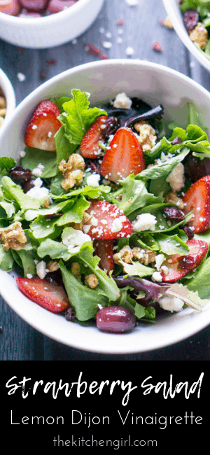 strawberry salad with spring mix in white bowl on grey wooden background with grapes and vinaigrette and title text (bottom of image)