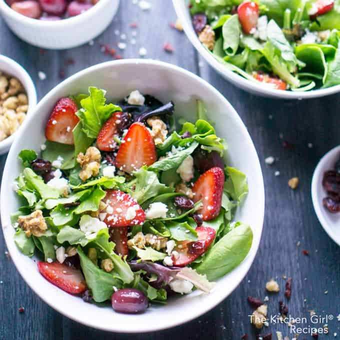 strawberry salad with spring mix in white bowl on grey wooden background with grapes and vinaigrette