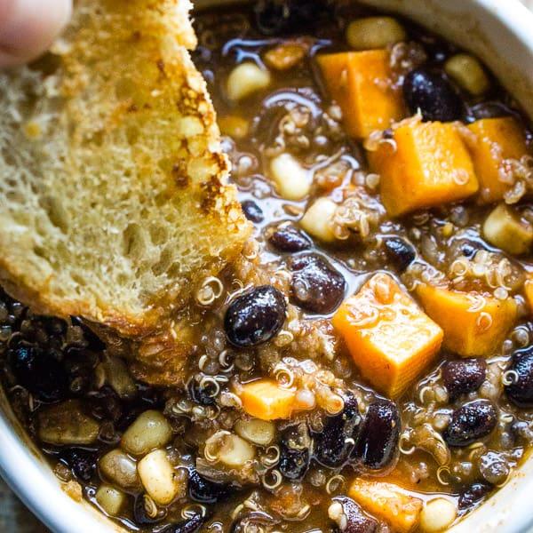sweet potato black bean chili with garlic bread in white bowl