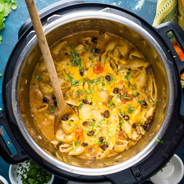 cheesy taco pasta in the Instant Pot on blue table with garnish and colorful napkin