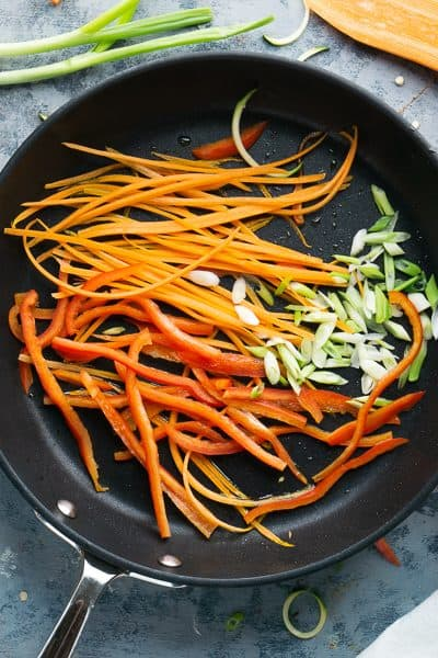 sliced carrots, bell peppers, and green onions in black skillet on blue background