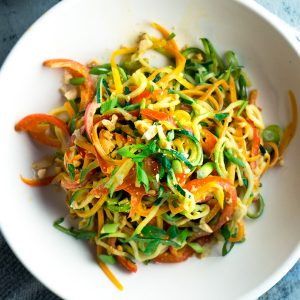 cooked spiralized vegetables in white bowl