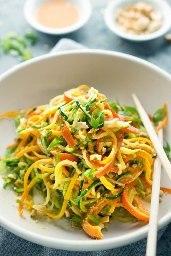 Spiralized zucchini noodles, carrots, and bell pepper are sauteed and tossed in a semi-spicy, vegan peanut butter sauce #vegan #thainoodles #asiannoodles #zucchininoodles #zoodles #lowcarb #mealprep #mealplan #peanutbuttersauce