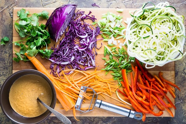 Thai zucchini noodles ingredients sliced into piles on wood cutting board: Cilantro, purple cabbage, green onions, zucchini noodles, red bell pepper, carrots, and peanut sauce