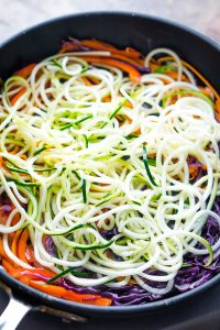 Pile of zucchini noodles over vegetables in black sauté pan