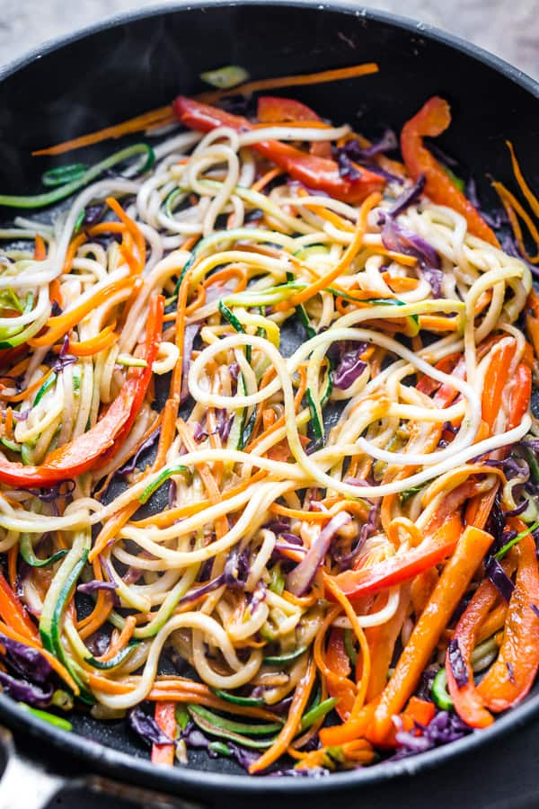 Thai zucchini noodle ingredients in black sauté pan coated with peanut sauce