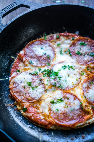whole pepperoni tortilla pizza in iron skillet on brown wooden background