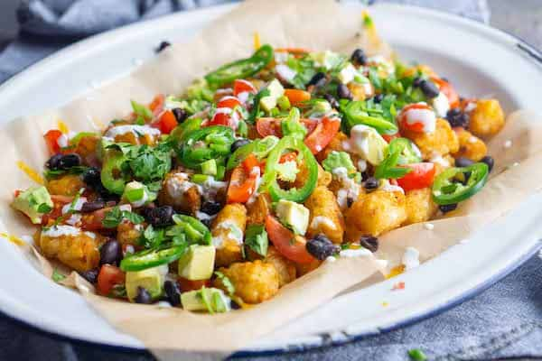 Totchos tater tot nachos on parchment covered white platter with blue linen