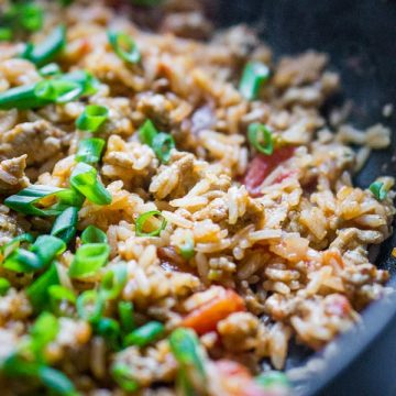 turkey taco meat and rice in skillet with tomatoes and green onions