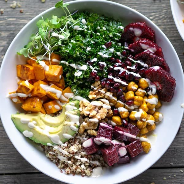 Buddha bowl with blood orange, pomegranate, beets, avocado, walnuts, turmeric chickpeas, sweet potatoes, kale, sprouts, quinoa, and creamy dressing in white bowl on wooden background