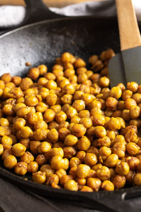 turmeric sautéed chickpeas in iron skillet being stirred with spatula