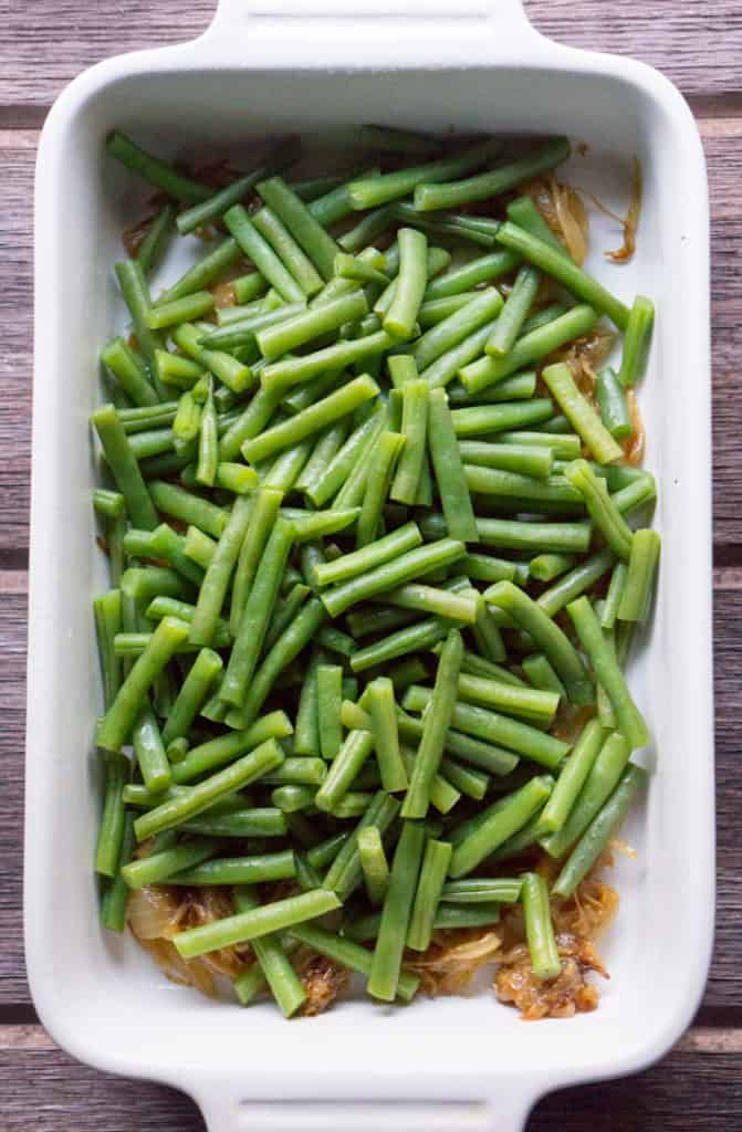 caramelized onions and steamed green beans in white ceramic baking dish on wood surface