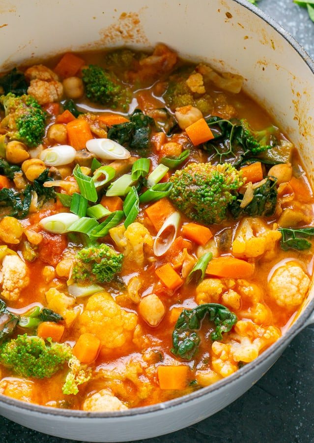 vertical close-up of vegan Thai coconut vegetable curry in white Dutch oven