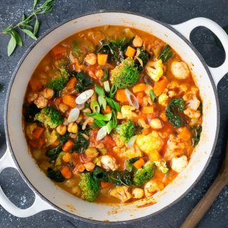 square image vegan Thai vegetable curry in white Dutch oven on black background with herbs, lime, and wooden spoon