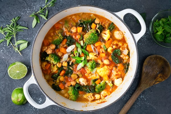 Vegan Thai vegetable curry in white Dutch oven on black background with herbs, lime, and wooden spoon