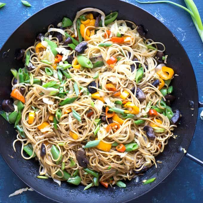 vegetable lo mein noodles in steel wok on blue background