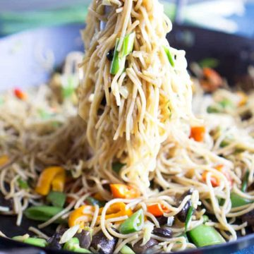 veggie lo mein noodles in black skillet being pulled up with tongs