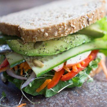 vegan vegetable sandwich piled up with vegetables on multigrain bread