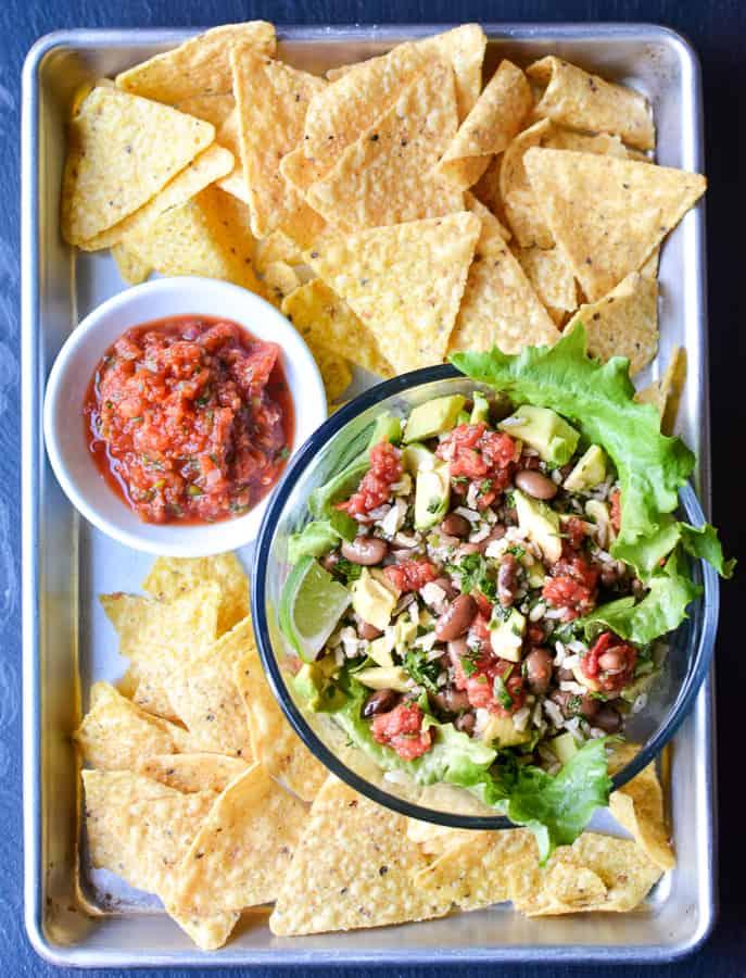vegetarian burrito bowl on baking sheet with tortilla chips and a bowl of salsa