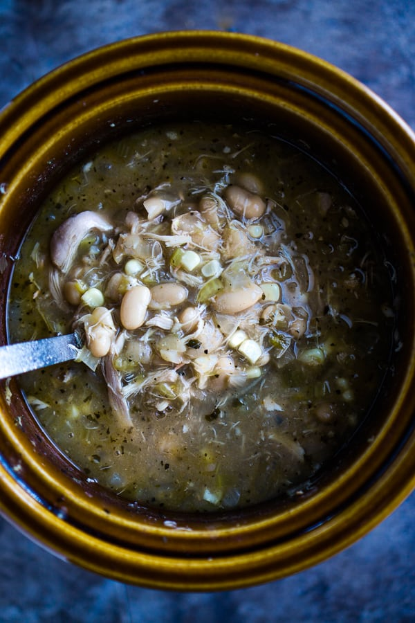 brown crockpot of white bean chicken chili on blue background