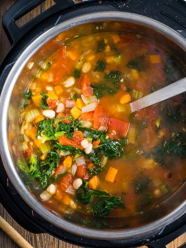 White bean kale soup with soup ladle in the Instant Pot