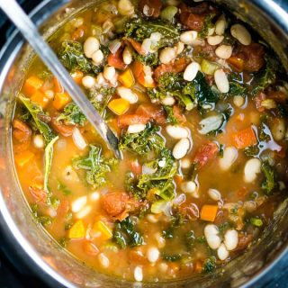 white bean kale soup in Instant Pot with ladle on wood table with scattered garlic and kale