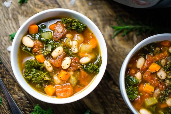 two small bowls white bean kale soup on wooden table