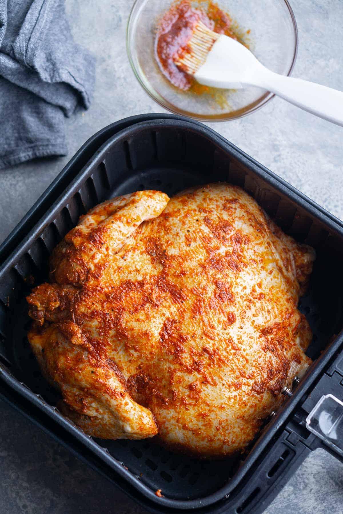 whole seasoned uncooked chicken in air fryer basket