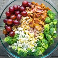 Broccoli salad ingredients with broccoli salad dressing in glass bowl on gray wood surface