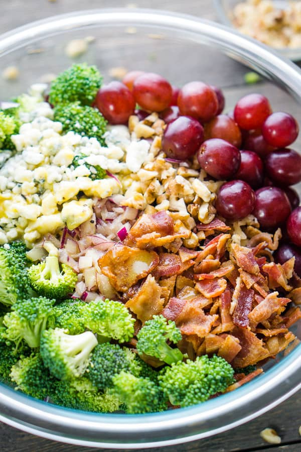 Broccoli salad ingredients in piles in glass bowl with Bowl of walnuts nearby on gray wood surface