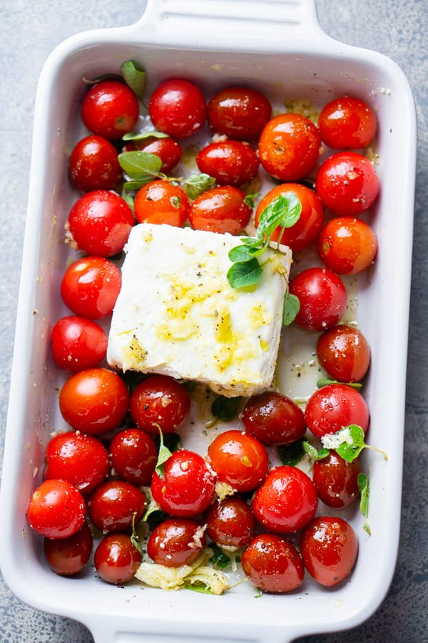 fresh herbs sprinkled over unbaked cherry tomatoes and feta cheese in white baking dish