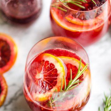 blood orange mimosas in two wine glasses next to bottle of blood orange juice, rosemary sprigs, and blood orange slices