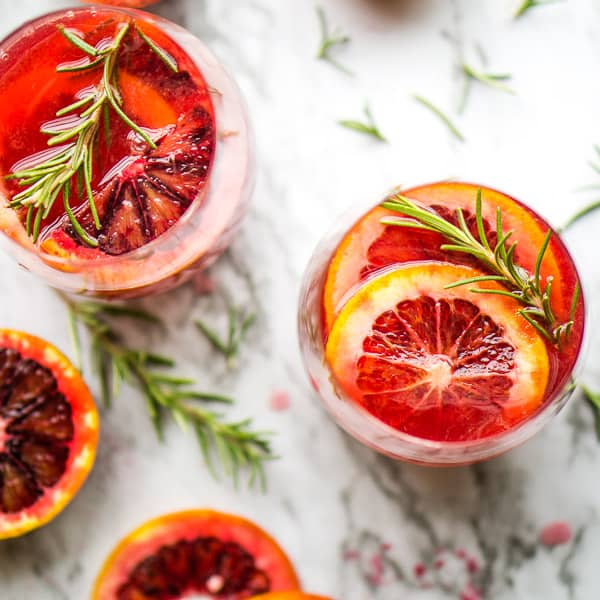 blood orange mimosas in two wine glasses next to rosemary sprigs and blood orange slices