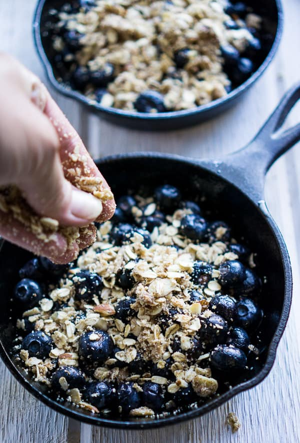 hand sprinkling topping on blueberry crisp in iron skillet on white wood surface