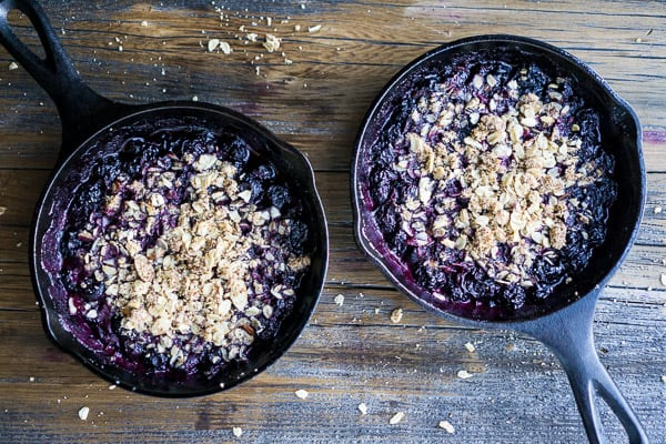 2 warm blueberry crisps in iron skillets on brown wood surface