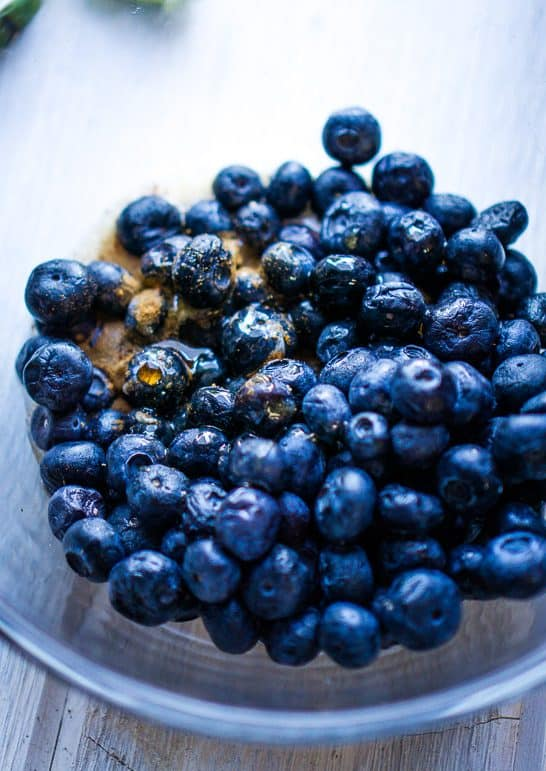 blueberries, cinnamon, and maple syrup in glass bowl on white surface
