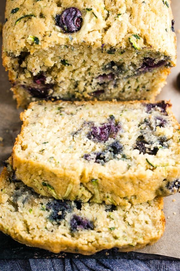 close up of thick-sliced blueberry zucchini bread laying on parchment paper