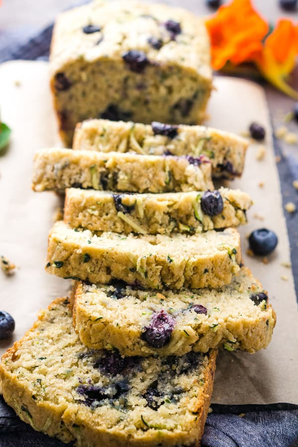 Thick-sliced blueberry zucchini bread on parchment-covered slate board on denim linen with fresh flowers and blueberries scattered
