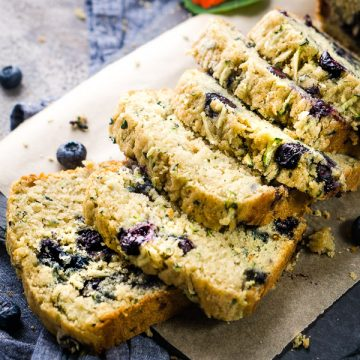 Thick-sliced blueberry zucchini bread on parchment covered slate board on denim linen