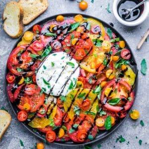 burrata and tomatoes on gray plate next to crostini and balsamic glaze