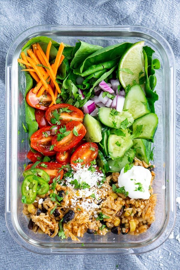 Glass meal prep container filled with burrito bowl ingredients. bowl sits on a blue linen