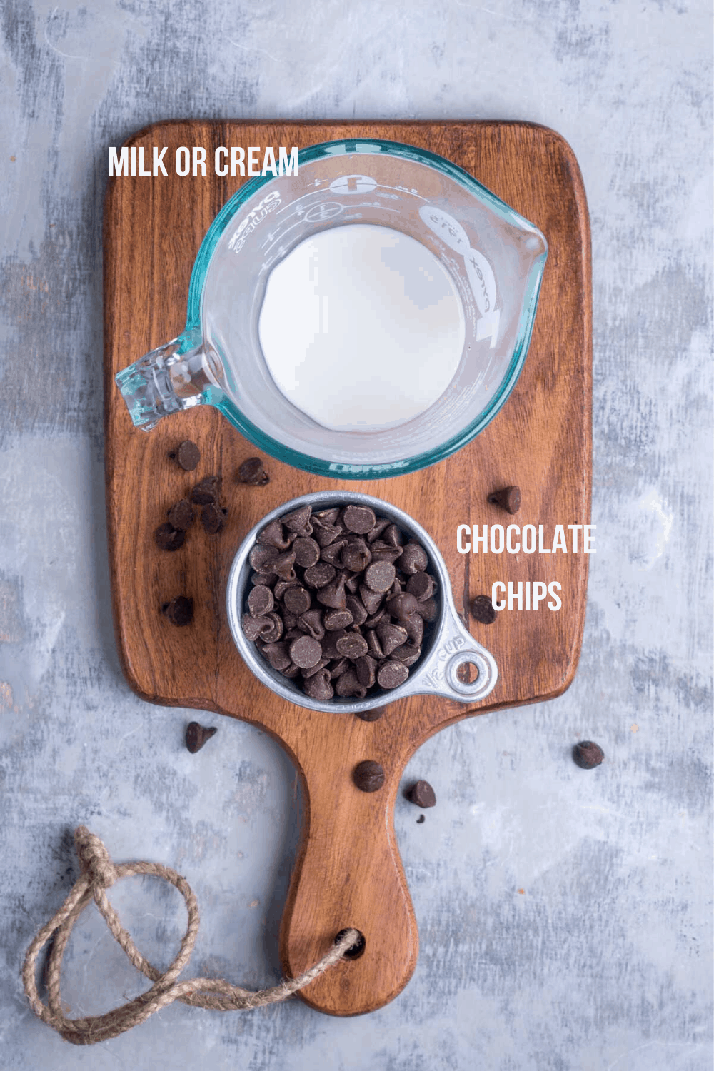 chocolate chips in tin measuring cup and milk in measuring cup on brown cutting board