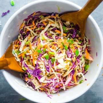 coleslaw ingredients in white bowl being tossed by wooden salad tongs