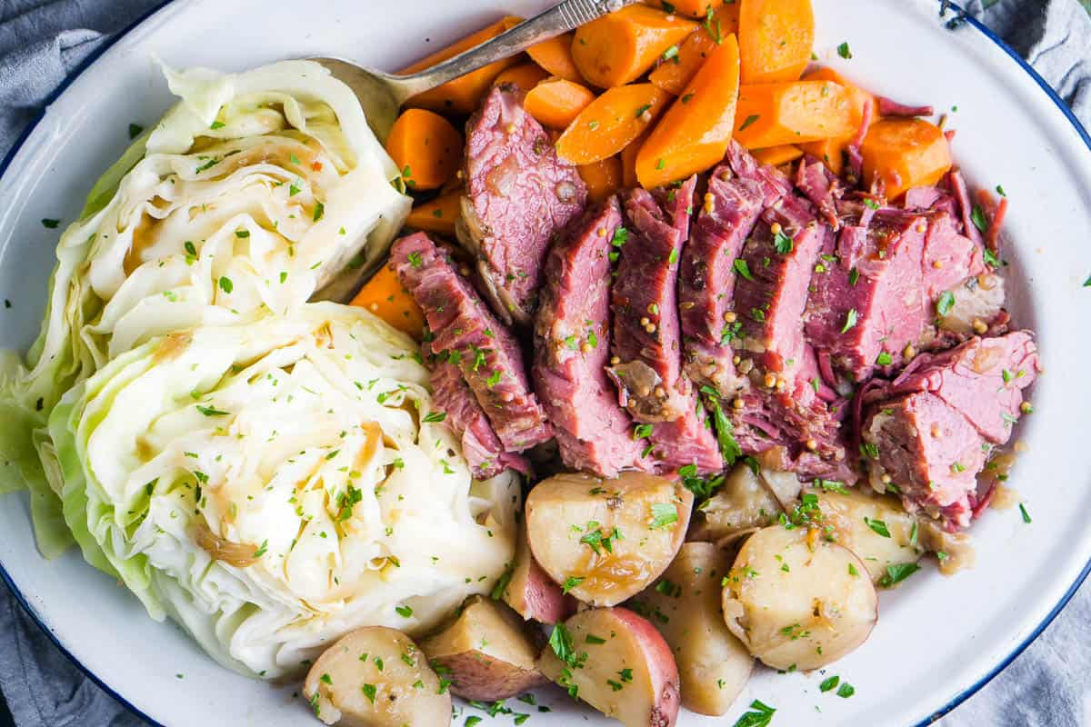 sliced corned beef brisket, potatoes, cabbage, and carrots on white serving platter