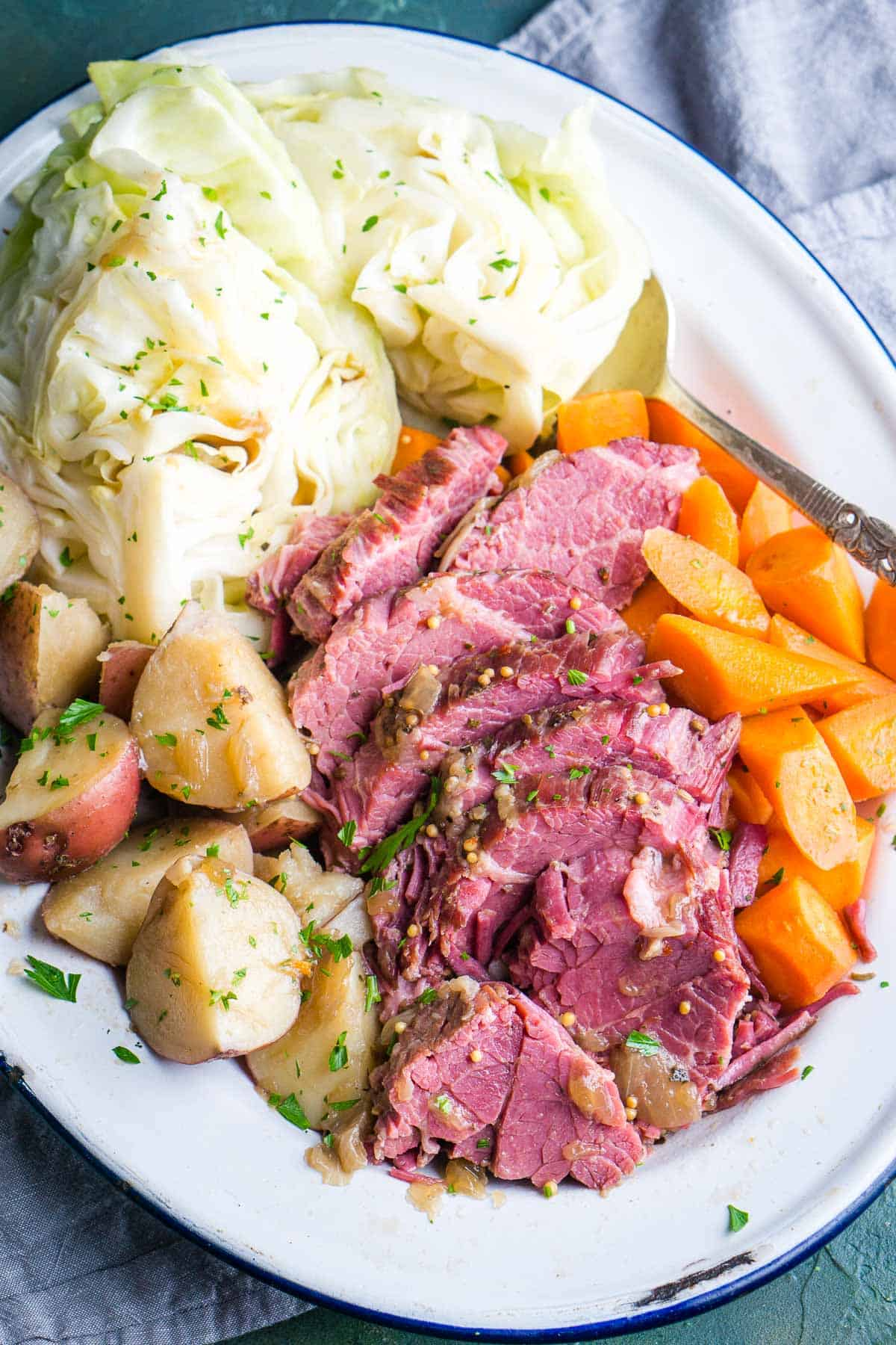 sliced corned beef and cabbage with potatoes and carrots on white serving platter
