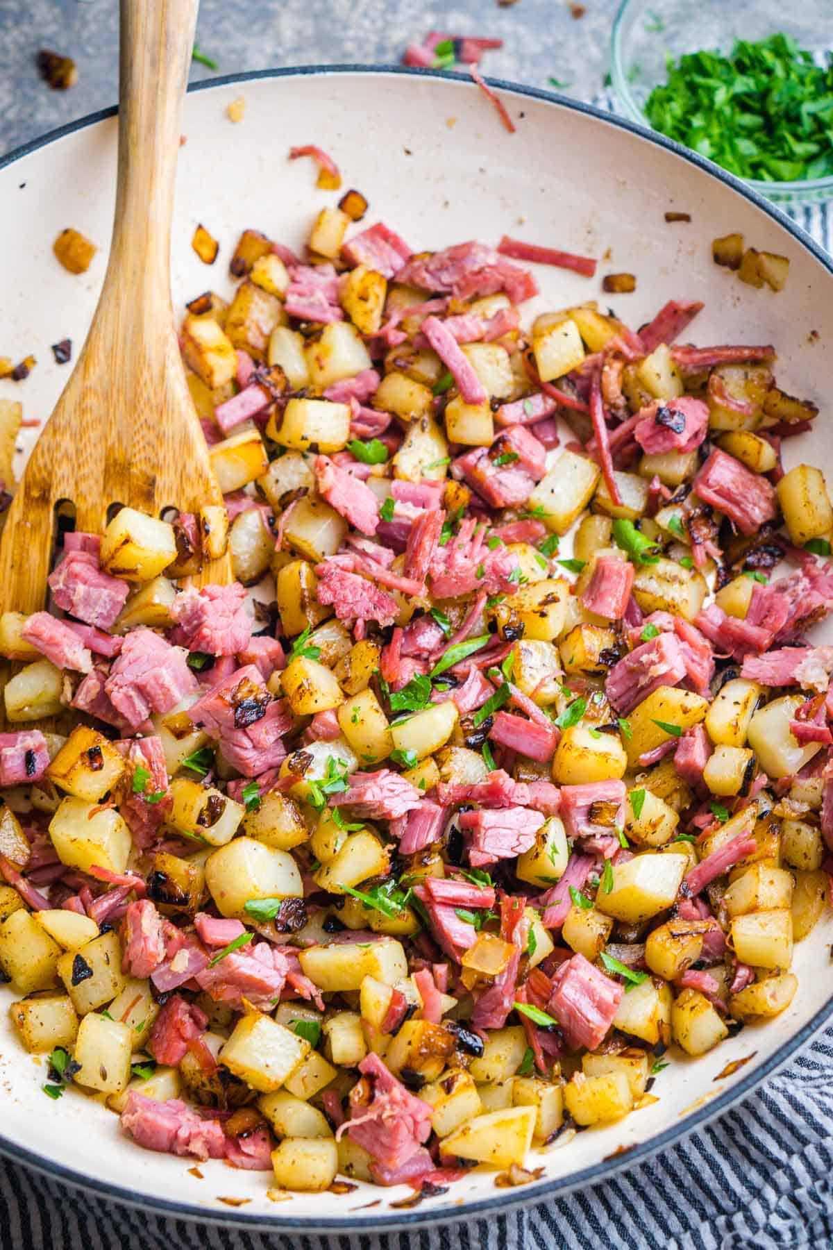 corned beef hash with wooden utensil in white skillet next to chopped parsley